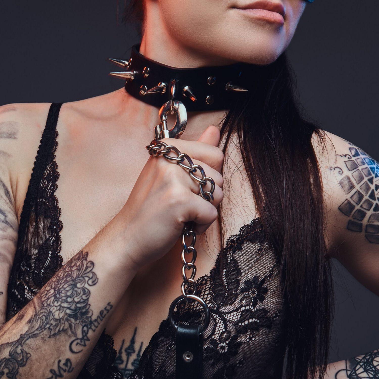 Close-up portrait of a sexy mistress girl wearing black lingerie in BDSM cat leather mask and accessories posing on a dark background.